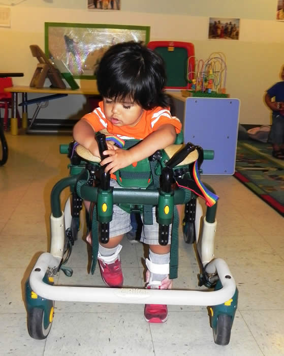 Boy standing up in his adaptive walker